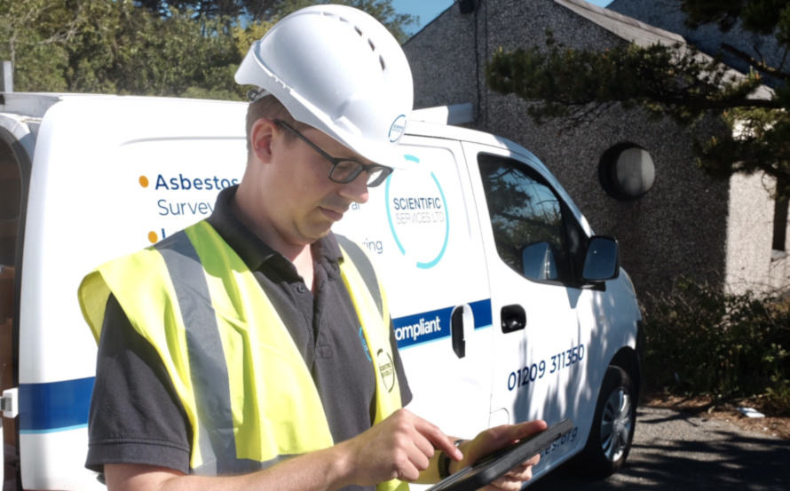 Surveyor looking at a tablet by a van after completing an asbestos survey